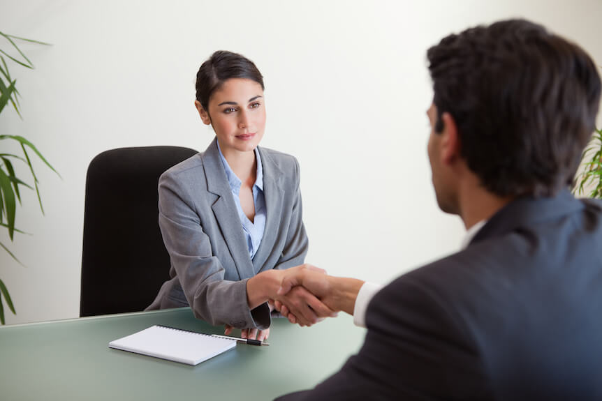 Two business people shaking hands to show the hire process.