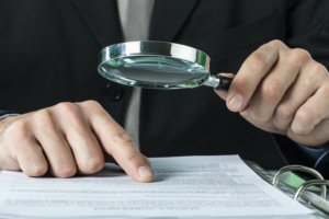 Man holding magnifying glass over paper to show an audit to see if Alignment of Courses to Degree.