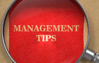 Management Tips . Magnifying Glass on Old Paper with Red Vertical Line.
