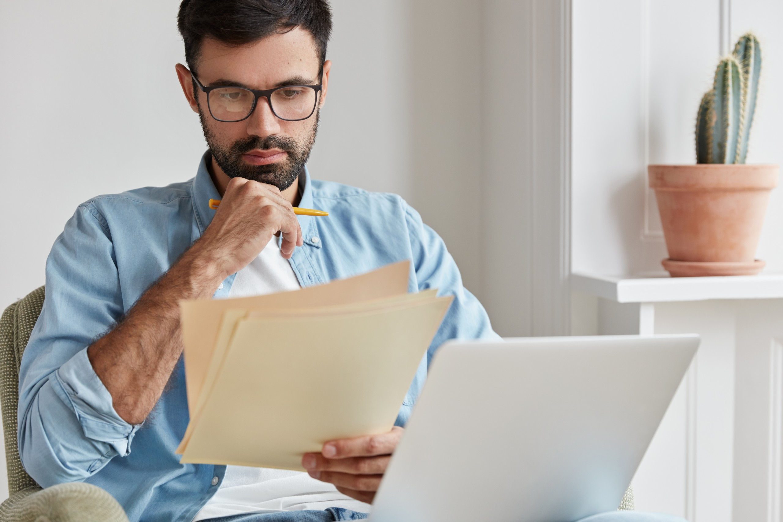 Man reading papers in front of laptop