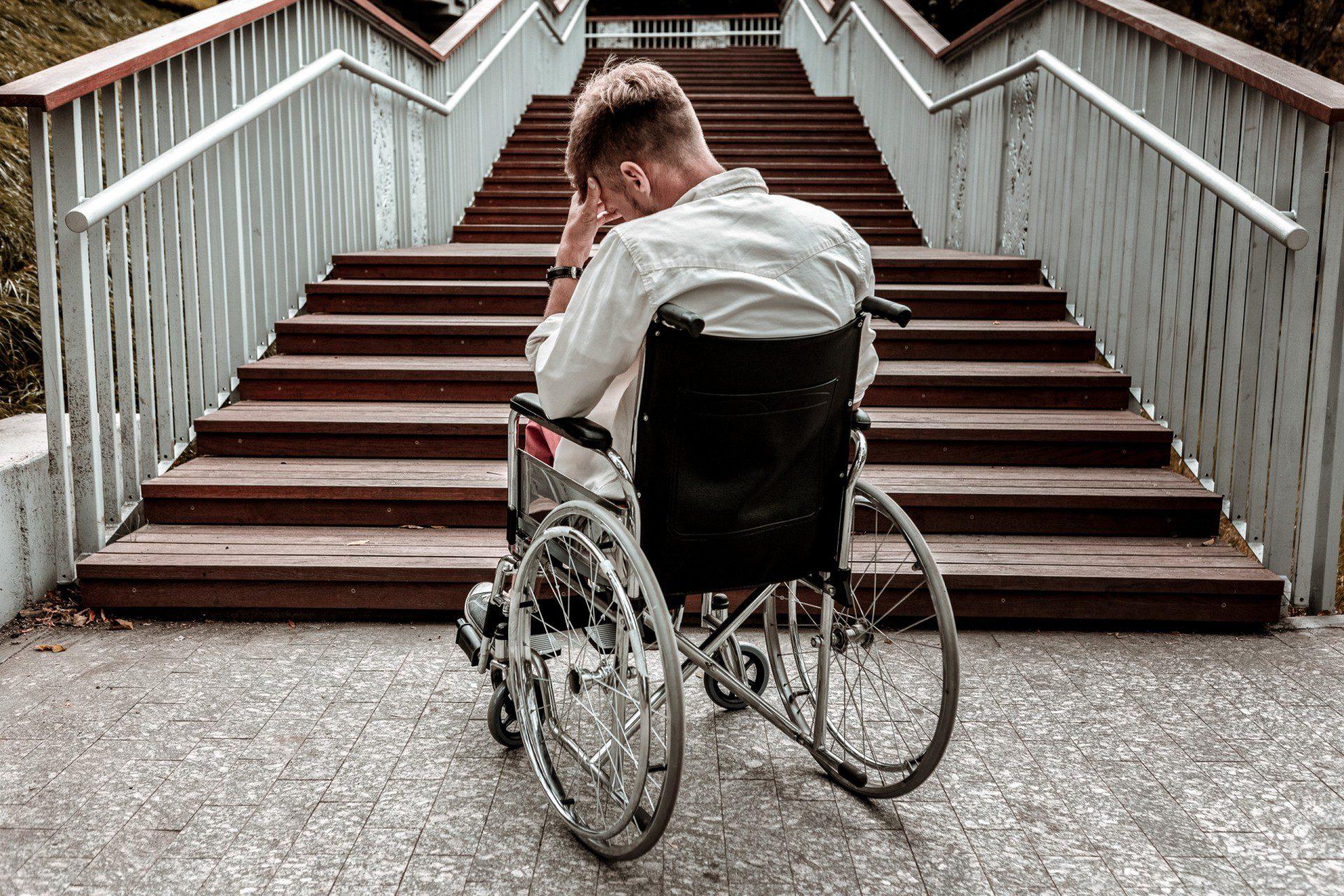 man in wheelchair facing long staircase