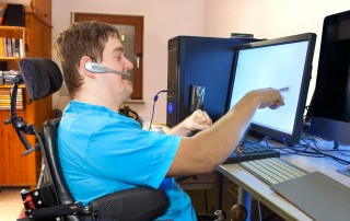 man using a touch screen and microphone headset for information and communication technology accessibility