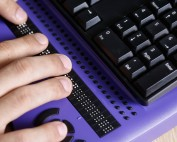 Hand using a braille keyboard for information and communication technology accessibility